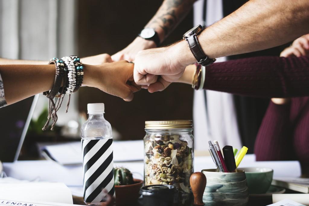 Fäuste, die symbolisch für gemeinsames Arbeiten und erfolgreiche Projekte im Coworking Space stehen