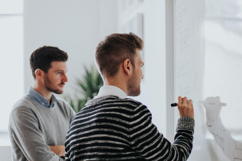 Zwei Männer, die im Coworking Space gemeinsam brainstormen und Notizen auf einem Whiteboard notieren